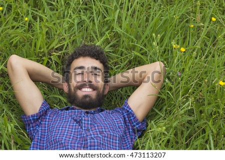 Happy young man smiling and lying on the grass with hands behind head.