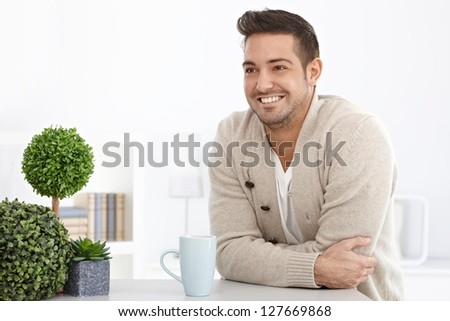 Happy young man smiling at home, looking away. - stock photo