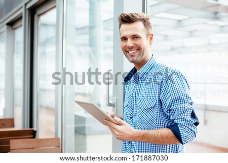 Happy young man smiling into the camera with a tablet in his hand