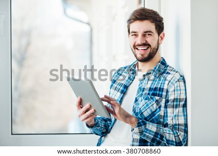 Happy young man smiling into the camera with a tablet in his hands - stock photo