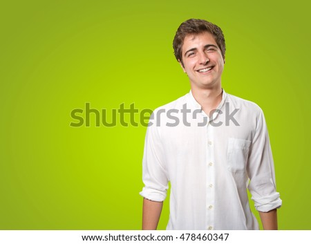 Happy young man smiling on green background
