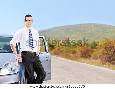 Happy young man standing by a car on an open road - stock photo