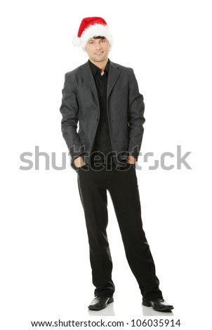 Happy young man standing, wearing suit and the Santa Claus hat. Isolated on the white background. - stock photo