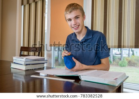 Happy young man surrounded by books selecting a pencil from his pencil case.