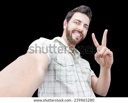 Happy young man taking a selfie photo isolated on black background - stock photo