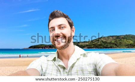 Happy young man taking a selfie photo on the beach - stock photo