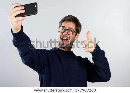Happy young man taking self portrait photography through smart phone over white background. - stock photo
