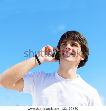 Happy Young Man Talking On Cellphone; Outdoors - stock photo