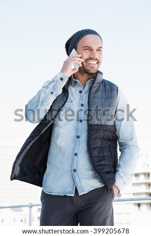 Happy young man talking on mobile phone - stock photo