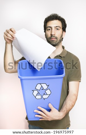 happy young man throw paper in blue basket with recycling logo