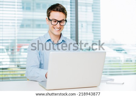 Happy young man typing on laptop
