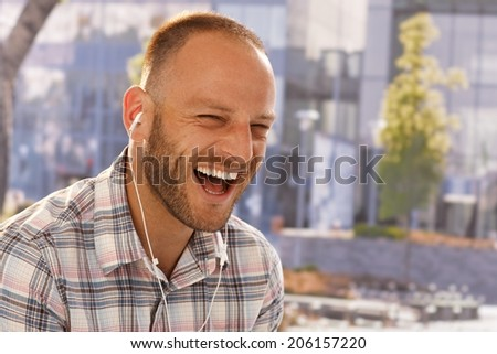 Happy young man using earbuds outdoors, shouting happy. - stock photo