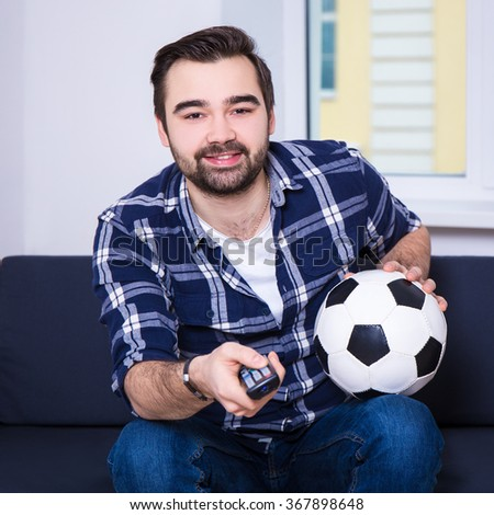happy young man watching soccer on tv - stock photo