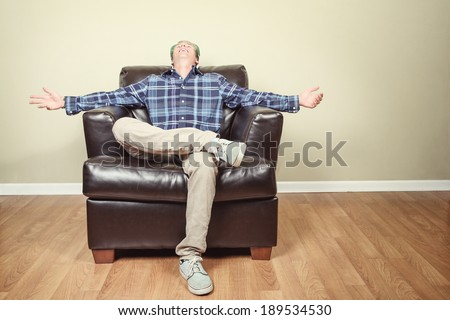 Happy Young Man wearing a hat, sitting in a chair - stock photo