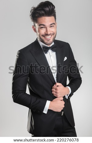 Happy young man wearing a tuxedo smiling for the camera while ajusting his jacket. on a grey background. - stock photo