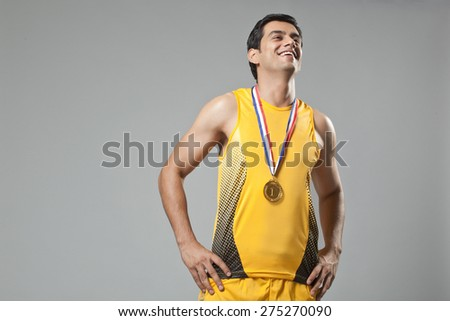Happy young man wearing gold medal with hands on hip isolated over gray background - stock photo