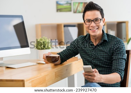 Happy young man with a cellphone looking at the camera - stock photo