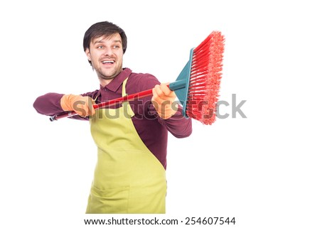 Happy young man with apron and gloves playing with a broom during cleaning process over white - stock photo
