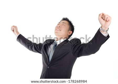 Happy young man with arms raised in the air isolated on white background
