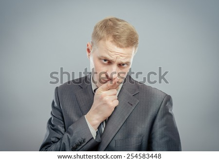 happy young man with finger near his mouth making silence - stock photo