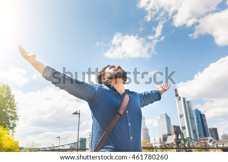 Happy young man with Frankfurt skyline on background. Middle eastern man with raised arms looking at the sky. Success and happiness concepts