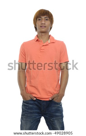 Happy young man with hands in pockets against white