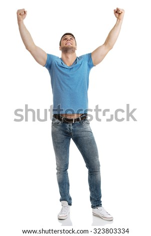 Happy young man with his arms up in victory gesture. - stock photo