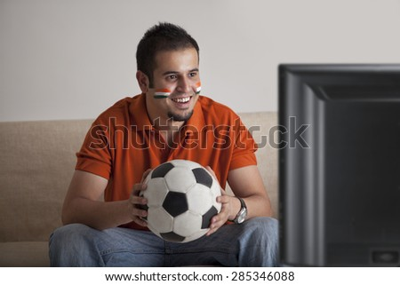 Happy young man with painted face watching television while holding soccer ball - stock photo