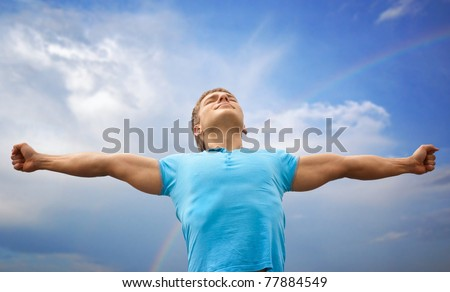 Happy young man with raised arms and closed eyes against blue sky - stock photo