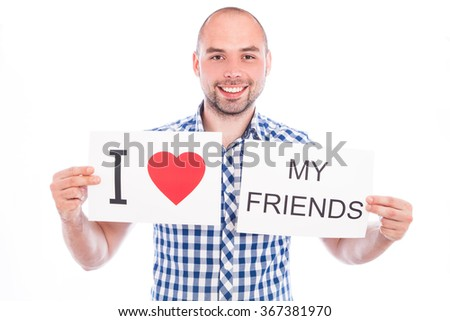 Happy young man with sign I love my  friends - stock photo