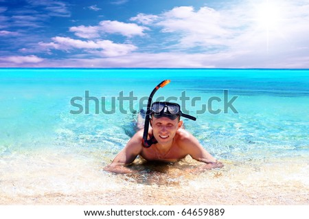 Happy young man with snorkelling on a sea beach
