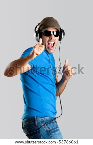 Happy young man with thumb up and listening music - stock photo