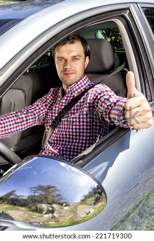 Happy young man with thumb up at the wheel of his car - stock photo