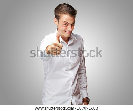 Happy Young Man With Thumbs Up On Gray Background