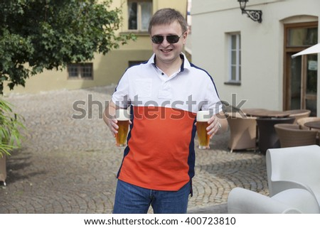 Happy young man with two glasses of beer - stock photo