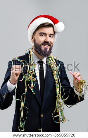 Happy young man, with violet beard, wearing in dark blue suit, santa heat and tie, posing on white background with ribbons on his shoulders and smiling, in studio, waist up - stock photo