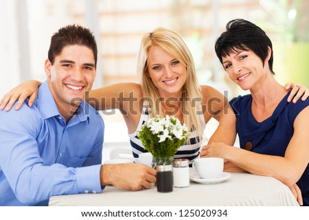 happy young man with wife and mother-in-law in cafe - stock photo