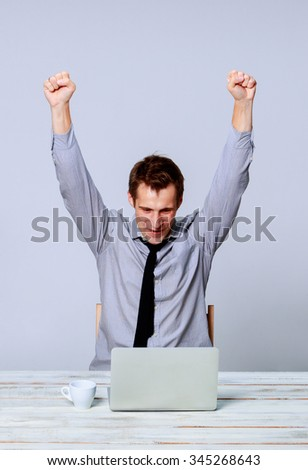 Happy young man working on laptop in the office on gray background