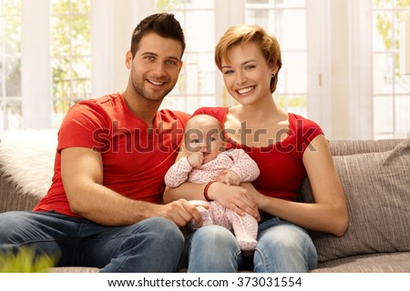 Happy young married couple holding baby girl on lap, smiling, looking at camera. - stock photo