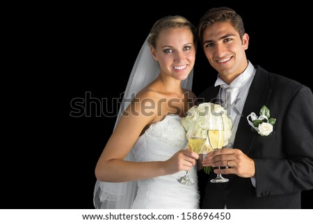Happy young married couple posing holding champagne glasses on black background - stock photo