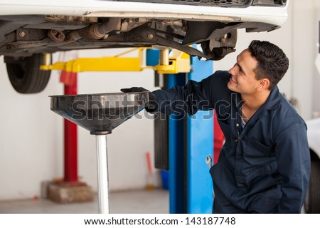 Happy young mechanic changing the oil of a car at an auto shop - stock photo