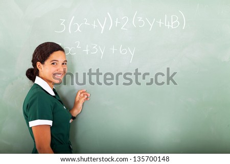 happy young middle school doing mathematics on the blackboard