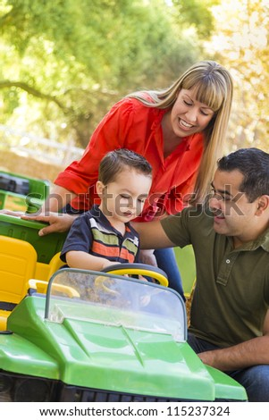 Happy Young Mixed Race Boy Enjoys A Toy Tractor While Parents Look On.