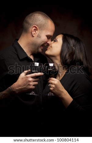 Happy Young Mixed Race Couple Holding Wine Glasses Against A Black Background.