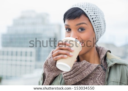 Happy young model in winter clothes enjoying coffee outside on a cloudy day - stock photo