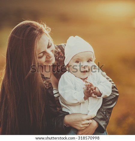 Happy young mom with lovely daughter at countryside. - stock photo