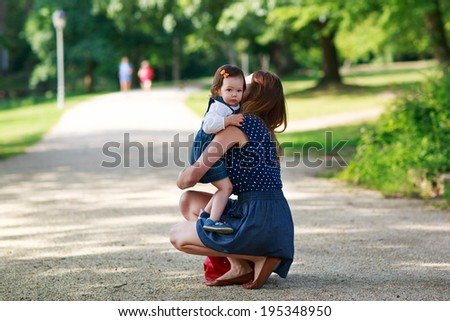 Happy young mother and adorable toddler girl walking through summer park and having fun together, outdoors. - stock photo