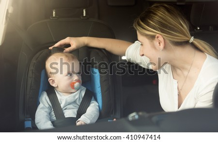 Happy young mother and baby in car child seat - stock photo