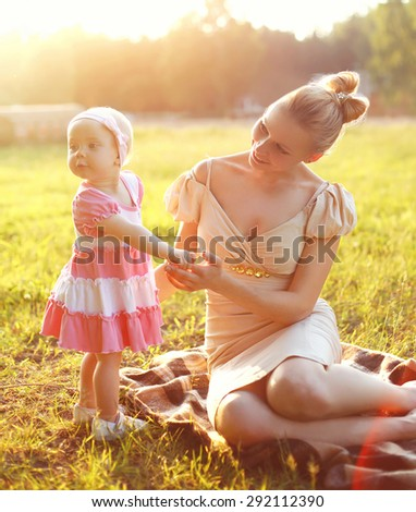 Happy young mother and baby little daughter wearing a dress together on the grass meadow in sunny summer day, evening sunset sunlight - stock photo
