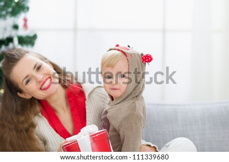 Happy young mother and baby spending Christmas time together - stock photo